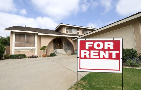 A home is being rented during tough economic times. Focus is on the sign.